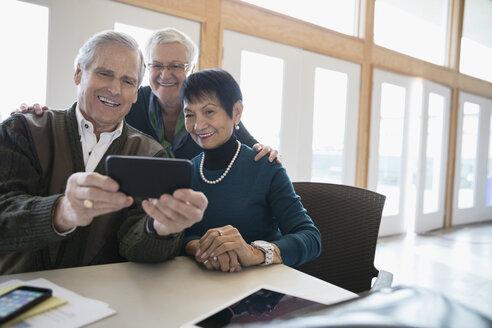 Smiling senior adult friends taking selfie with smart phone - HEROF32880