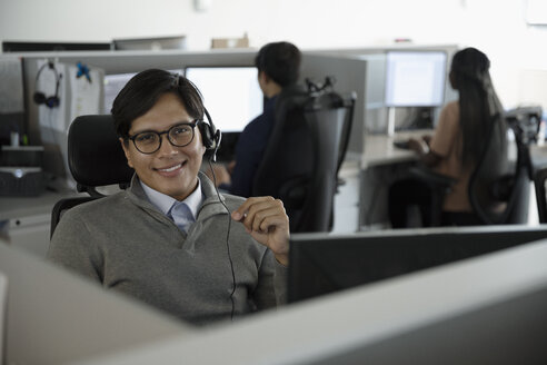 Portrait confident man wearing headset, working in call center - HEROF32992