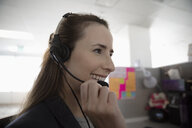 Smiling woman wearing headset, working in call center - HEROF32995