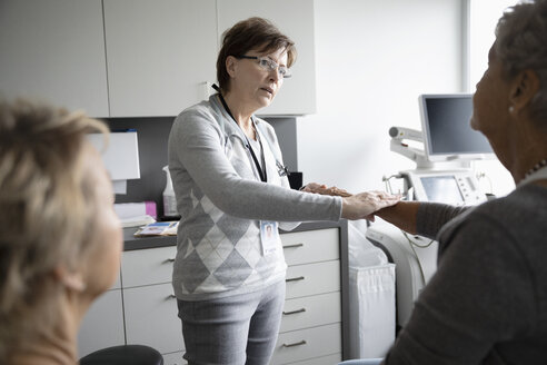 Female doctor examining arm of senior patient in clinic examination room - HEROF33022