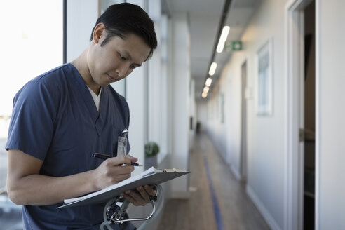 Focused male nurse reviewing notes on clipboard in clinic corridor - HEROF33103