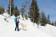 Germany, Bavarian Forest, Lusen, smiling woman with dog hiking in winter - MAEF12830