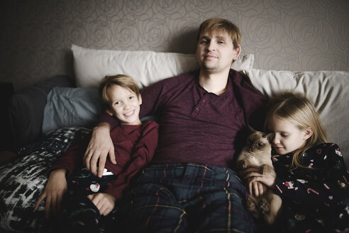 Portrait of father, two children and cat relaxing together at home - EYAF00069