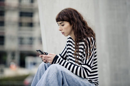 young woman wearing striped shirt, using smartphone - FLLF00085