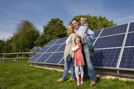 Smiling family standing together near large solar panels - JUIF00761