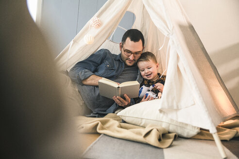 Father and son reading a book together in tent at home - UUF16854