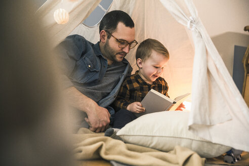 Father and son reading a book together in tent at home - UUF16857