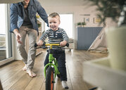 Father helping son riding with a balance bicycle at home - UUF16875