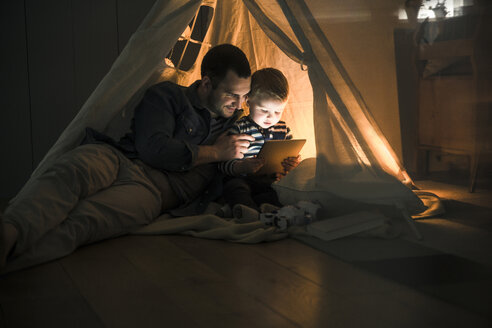 Father and son sharing a tablet in a dark tent at home - UUF16878