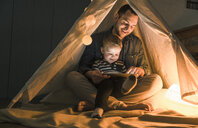 Father and son sharing a tablet in a dark tent at home - UUF16884