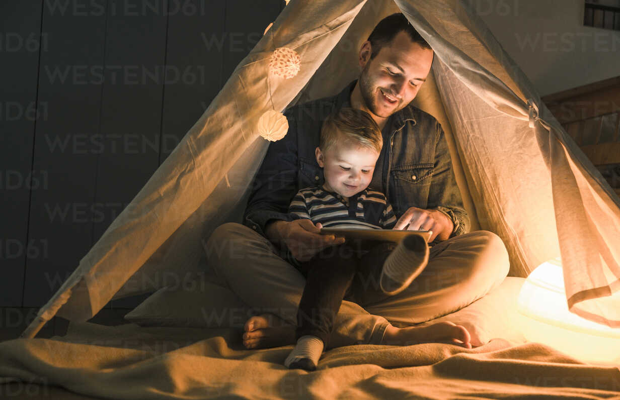 Father and son sharing a tablet in a dark tent at home - UUF16884 - Uwe Umstätter/Westend61