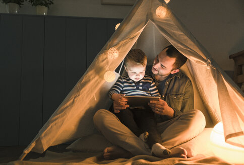 Father and son sharing a tablet in a dark tent at home - UUF16887