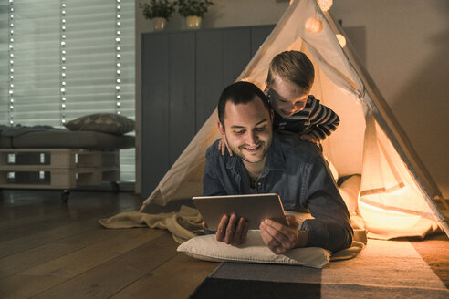 Father and son sharing a tablet at an illuminated tent at home - UUF16890