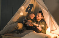 Father reading book to son at an illuminated tent at home - UUF16893