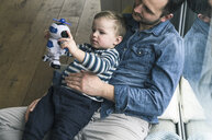 Father and son playing with a toy robot at home - UUF16899