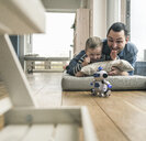 Excited father and son lying on a mattress at home watching a toy robot - UUF16905