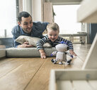 Excited father and son lying on a mattress at home watching a toy robot - UUF16908