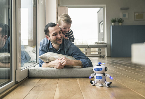 Excited father and son lying on a mattress at home watching a toy robot - UUF16911