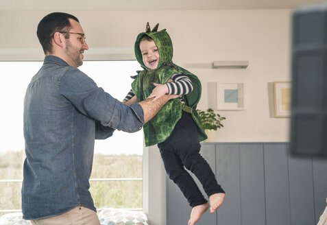 Father playing with happy son in a costume at home - UUF16932