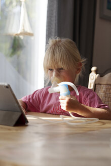 Portrait of blond little girl using asthma inhaler while looking at digital tablet - GAF00100