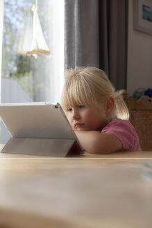 Portrait of sad little girl using digital tablet at home - GAF00103