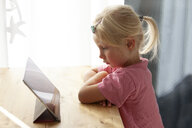 Profile of blond little girl using digital tablet at home - GAF00106