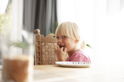 Portrait of tricksy little girl sitting at dining table eating - GAF00109