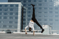 Artist doing handstand on roof terrace - AFVF02650