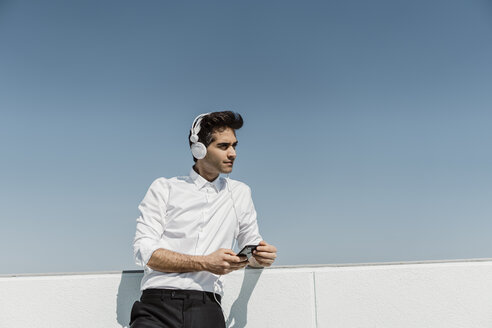 Portrait of businessman listening music with headphones and smartphone on roof terrace - AFVF02671