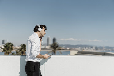 Spain, Barcelona, businessman listening music with headphones and smartphone on roof terrace - AFVF02677