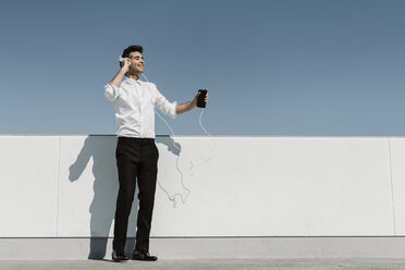 Happy businessman listening music with headphones and smartphone on roof terrace - AFVF02680