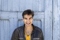 Portrait of laughing man in front of lightblue wooden door - AFVF02701