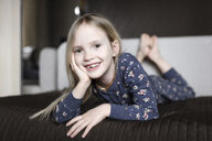 Portrait of smiling little girl with tooth gap relaxing on couch at home - EYAF00082