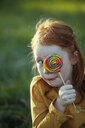 Grimacing girl covering her eye with a lollipop - GAF00114