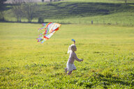 Little girl running in field with kite - GAF00117