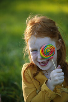 Happy girl covering her eye with lollipop - GAF00129