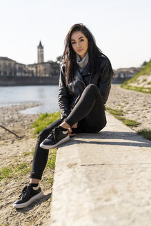 Italy, Verona, portrait of young woman sitting at the riverside - GIOF05962