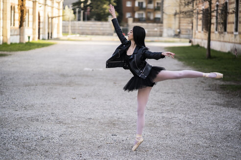 Italy, Verona, Ballerina dancing in the city wearing leather jacket and tutu - GIOF05992