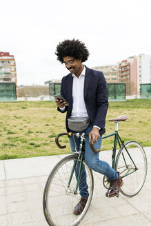 Spain, Barcelona, smiling businessman on bicycle using cell phone in the city - VABF02252