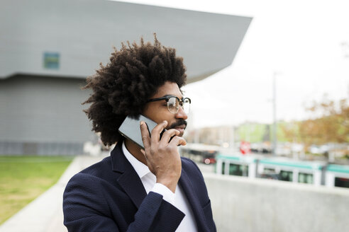 Spain, Barcelona, portrait of businessman on cell phone in the city - VABF02255