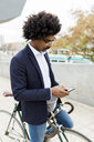 Spain, Barcelona, businessman on bicycle using cell phone in the city - VABF02258