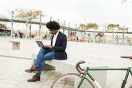 Spain, Barcelona, businessman with bicycle in the city sitting on bench using laptop - VABF02273
