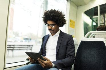 Spain, Barcelona, businessman in a tram using tablet - VABF02300