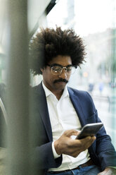 Spain, Barcelona, businessman in a tram using cell phone - VABF02303