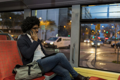 Spain, Barcelona, businessman in a tram on cell phone - VABF02324