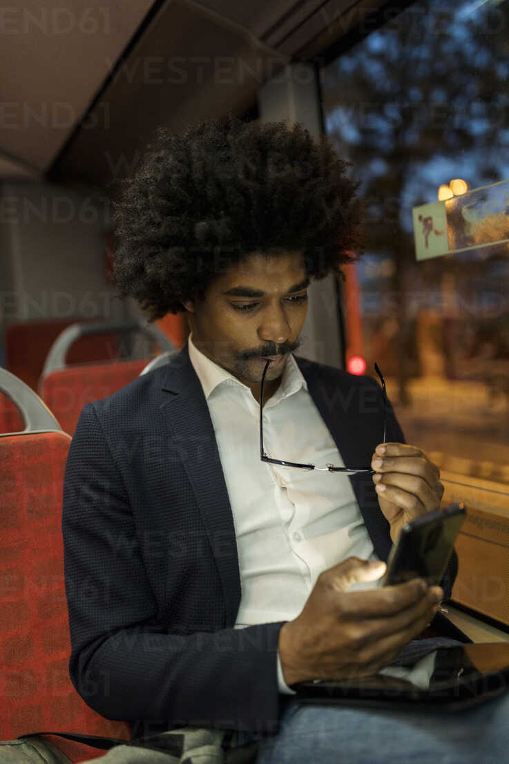 Spain, Barcelona, businessman in a tram at night using cell phone - VABF02327 - Valentina Barreto/Westend61