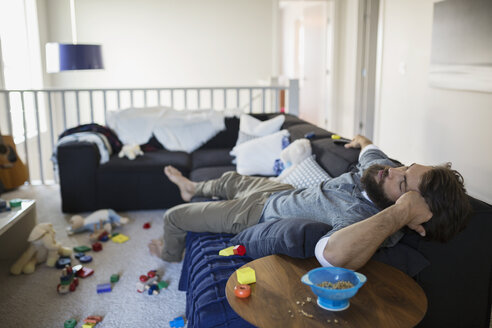 Exhausted man napping on sofa surrounded by toys - HEROF33106