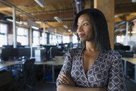 Confident businesswoman looking away in office - HEROF33112