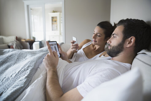 Couple using cell phone and digital tablet bed - HEROF33166