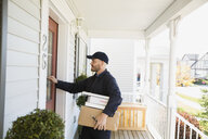 Delivery man with packages knocking at front door - HEROF33220